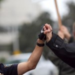 Police officer and marcher clasp hands. Photo by Tracy Sydor.